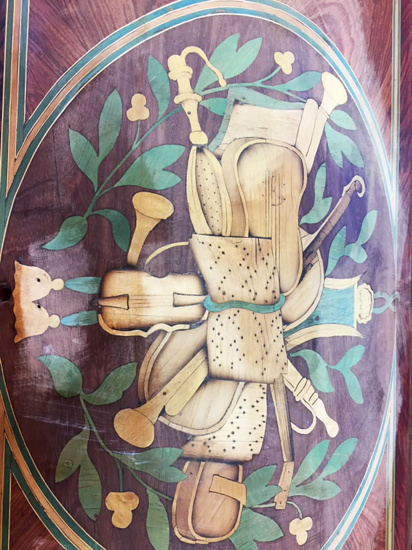 Détail de la marqueterie florale figurant les attributs de la musique