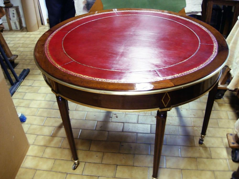 Table ronde après restauration et pose d'un cuir rouge
