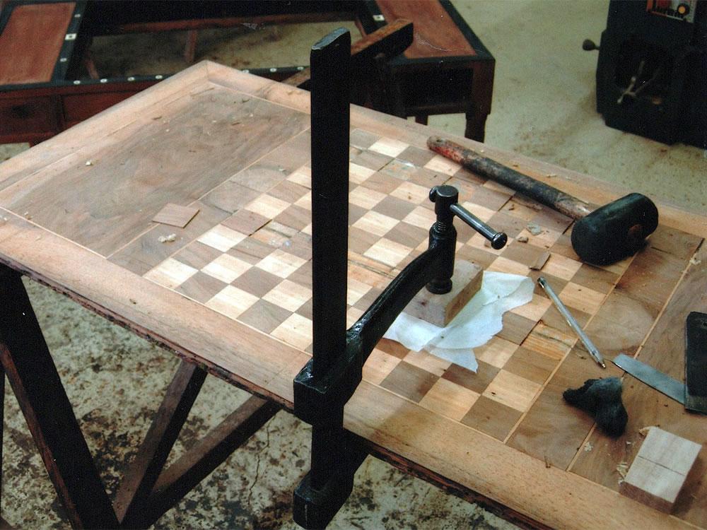 Restauration d'une table de tric dans l'atelier d'ébénisterie